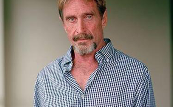 A cleaned-up John McAfee posing for photographs in 2015