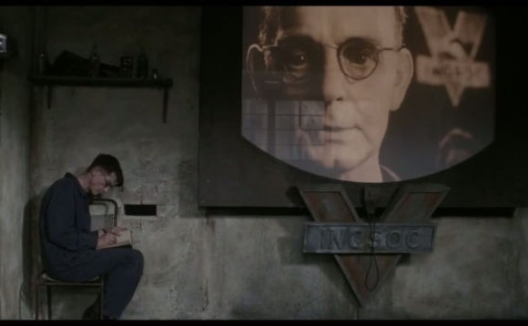 Winston Smith sits reading underneath the gaze of Big Brother...