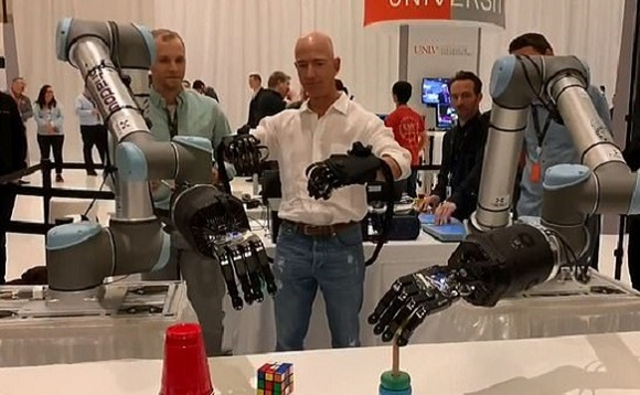 "Jeff Bezos playing with large robotic arms at ""re: MARS"" event. Image via Twitter/Jeff Bezos"